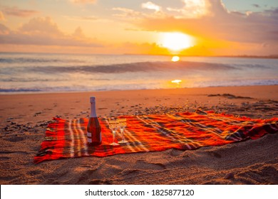Red plaid on the beach with wineglasses and bottle of white wine at sunset