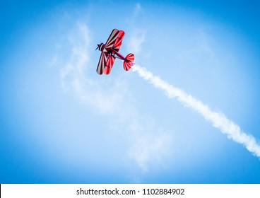 Red plane with propeller flying upward with white smoke on the tail in the blue sky
