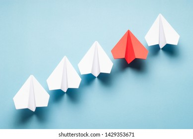Red plane and white plane on blue background. Red and white origami planes. Minimalist composition with paper planes.