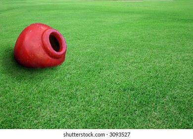 Red planter pot on a field of green grass.