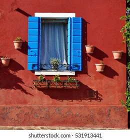 Red plastered wall with opened window which  surrounded the blue wooden shutter and clay pots with blooming flowers on the famous island Burano, Venice. Warm sunset light.