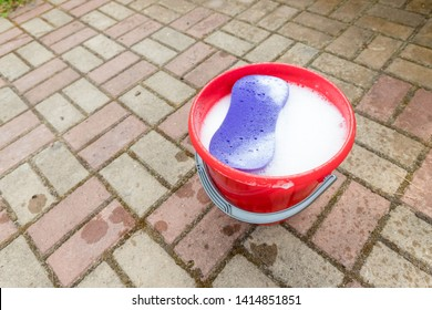 A red plastic bucket on cobblestone background with purple colored sponge. Cleaning theme.Household equipment at home interior background, spring-cleaning, tidying up, cleaning service concept