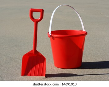 A red plastic bucket and spade on the beach