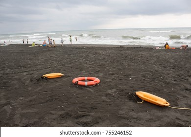 red plastic floatation rescue devices and sunbeds on beach. the weather is dull. safety vacation, overcast, rescue tool