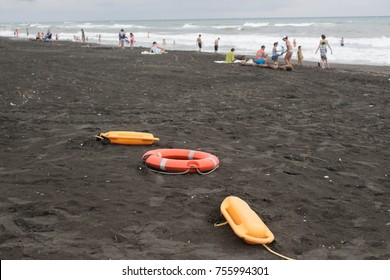 red plastic floatation rescue devices and sunbeds on beach. rainy weather, overcast. Travel or sea vacations concept