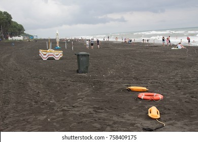 red plastic floatation rescue devices and sunbeds on beach. cloudy weather, overcast. safety vacation, rescue tool