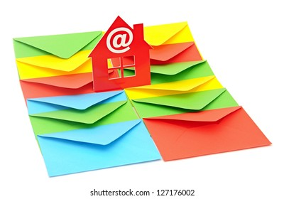 red plastic house shaped object on colorful envelopes white background