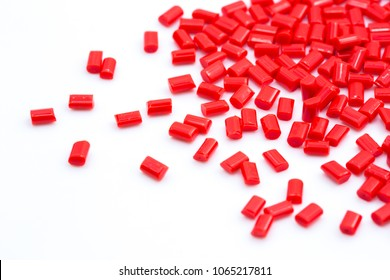 Red plastic polymer granules on white background.