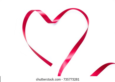 Red plastic ribbon heart shape on white background.