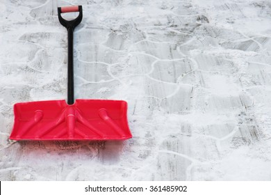 Red plastic shovel for snow removal. Winter is coming.