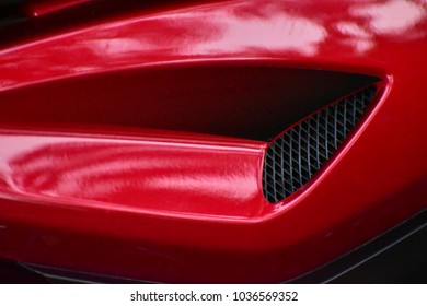 Red plastic side cover of a motor bike isolated object stock photograph