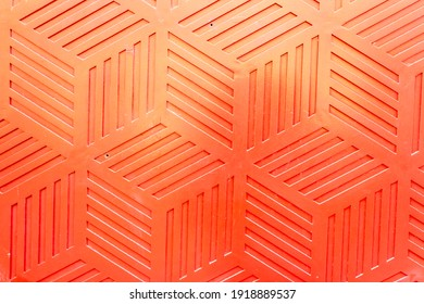 Red plastic surface with repetitive geometric shapes. Seamless geometrical patterns with rhombuses, lines and corners. Stamped plastic surface with simple geometric lines. Space for inserting text