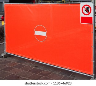 Red plastic tarpaulin with painted a  no entry sign in the center, used to temporarily prohibit access. A second signpost is hanging on the top right. Copy space for text.