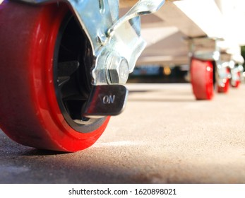 Red plastic trolley wheels On a cement floor background. selective focus