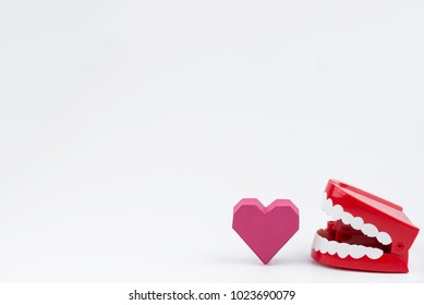 Red Plastic Wind Up Chattering Teeth biting paper box red heart shape at Valentine's Day.Concept Valentine's Day, Day of love