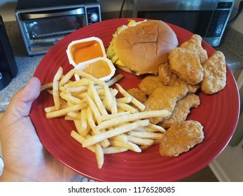 red plate with french fries, chicken, and dipping sauces in a kitchen