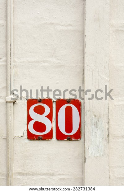 Red plate numbers Number 80 eighty on white painted surface closeup