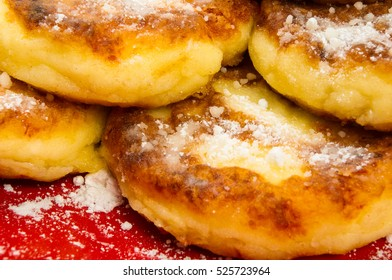 red plate of pancakes in powdered sugar on black background