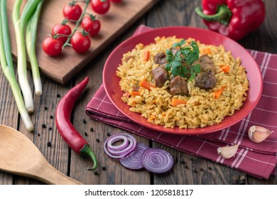 Red plate with pilaf on a rustic brown wooden table. On the table there are red pepper, green onions, garlic, cherry tomatoes, red napkin, spoon.