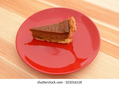 Red plate with a slice of tasty pumpkin pie on a pine table
