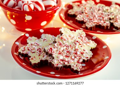 Red plate of snowflake shaped chocolate peppermint bark candies with tiny holiday lights