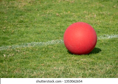 A red playground ball sits next to the white line on a green grass field.