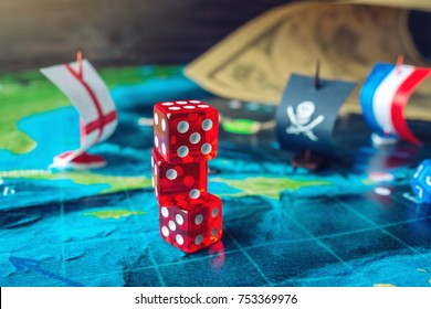 Red playing bones on the world map of the field handmade Board games with a pirate ship. The game of battleship.