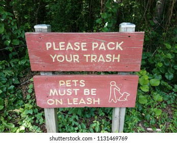 red please pack your trash sign and pets must be on leash sign near trail
