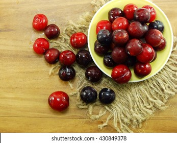red plum on wooden background top view