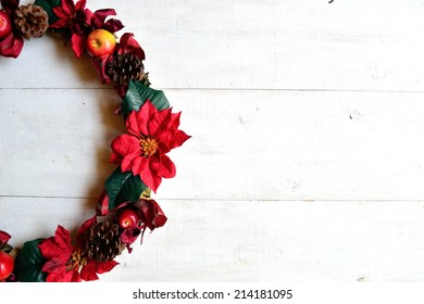 Red poinsettia Christmas wreath on white wooden background