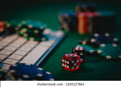 Red poker side on focus. Side view of a green poker table with some poker chips on a keyboard. Playing poker online addiction. Betting money on Internet at home. Lucky concept.