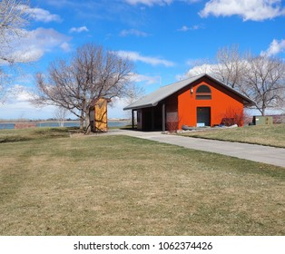 Red pole barn by a lake and grass area