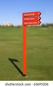A red pole with sign arrows, pointing directions in a golf course: Driving Range, Putting Green, Short Game Area, over a clear blue sky with a blurred fairway on background