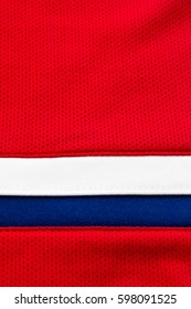 Red polyester with blue and white stripes, close up of a hockey jersey