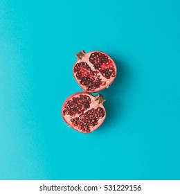 Red pomegranate fruit on pastel background. Minimal flat lay concept.