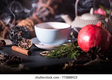 red pomegranate on a dark background, green rosmary and dried flowers, cup of tea and teapot