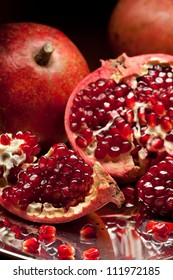 Red pomegranate slices and ripe seeds on silver salver