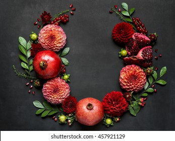 Red pomegranates and dahlias form a dramatic floral arrangement on a dark textured background for Rosh Hashanah the Jewish New Year