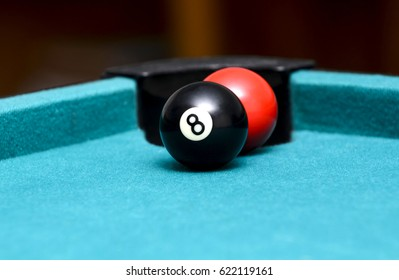 Red pool ball behind the eight ball