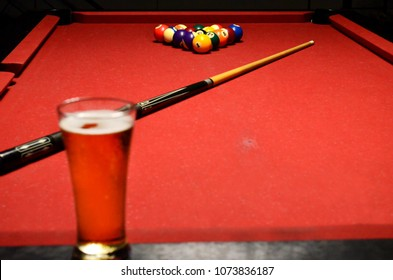 Red Pool Table With Cue And Beer In Glass On Foreground