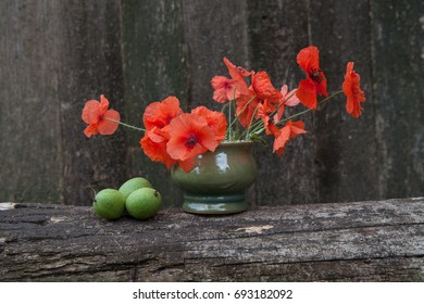 Red poppies in a green vase on a background of a wooden texture background