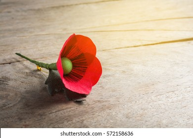 Red Poppy Flower made from fabric on wooden background, symbol of war - for Remembrance Day,  remembrance day, veteran's day, lest we forget