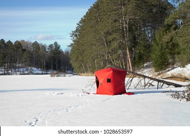 A red portable ice fishing shelter on a remote Minnesota lake on a sunny afternoon