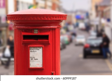 A red post box set against a de-focused city centre background
