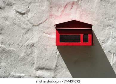 Red postbox have long shadow shining down on white cement wall.