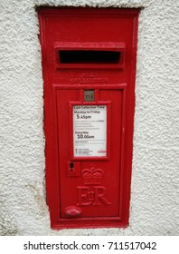 Red postbox on the white wall at Alnmouth England, taken on 15th August 2017