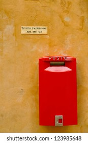 "Red postbox on a yellow wall in Volterra, Tuscany, Italy. Marble sign says ""Post no bills"""