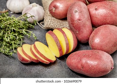 Red potato on black wood table in kitchen. With spice and garlic. Preperation for cooking.