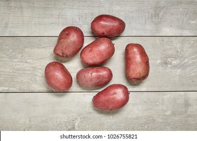 Red potato on black wood table in kitchen. Preperation for cooking.