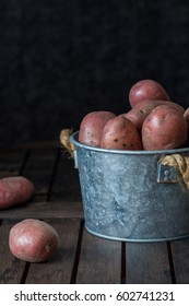 Red potatoes in bucket on the old table